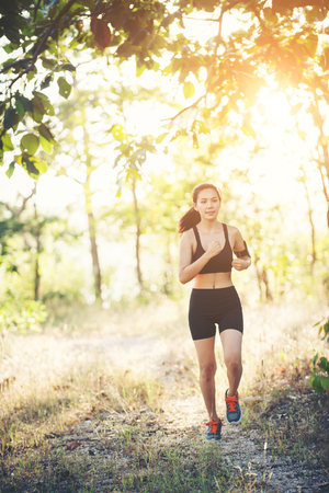 Young woman jogging on rural road in forest nature.