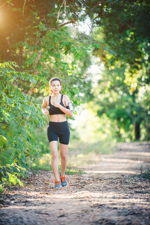 mujer mirando el horizonte: Young fitness woman running on a rural road. Sport woman running,Healthy lifestyle concept. Foto de archivo