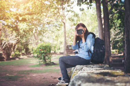 Young attractive woman photographer tourist with backpack coming to shoot photo at ancient phanom rung temple in thailand.