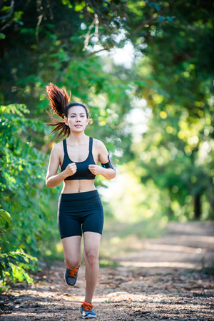Young fitness woman running on a rural road. Sport woman running,Healthy lifestyle concept. Imagens - 77501053