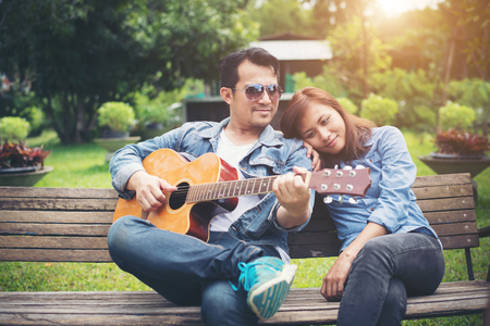 Young couple in love playing acoustic guitar in the park while sitting on the bench together. Stock Photo