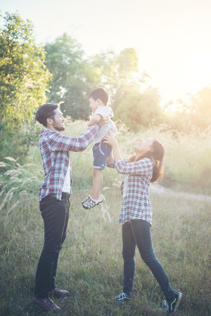 Happy young family spending time together outside in green nature park. Family love concept. Imagens - 77501052
