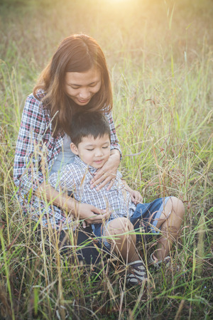 Mommy hugging her little boy. Family walking in the field. Outdoors. Family value concept.