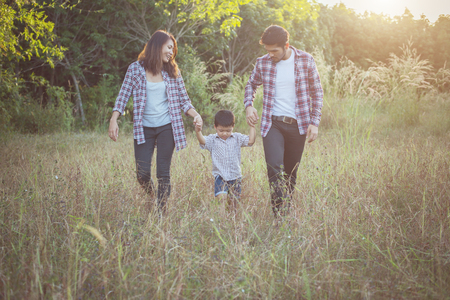 Happy young family spending time together outside in green nature park. Family love concept. Imagens - 77501050