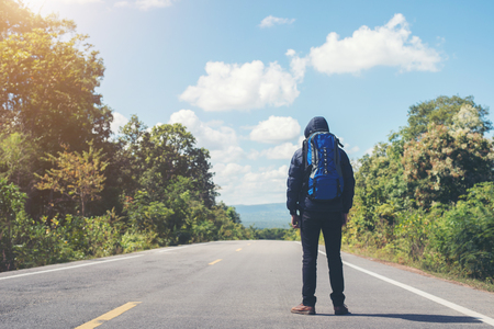 Rear of hiker man walking on the rural road on vacation. Holiday tourism concept. Imagens - 77501058