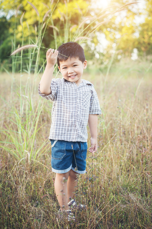 Happy little asian boy playing outdoors. Enjoy life. Cute asian boy on field. Imagens