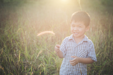 Happy little asian boy playing outdoors. Enjoy life. Cute asian boy on field. Imagens - 77501067