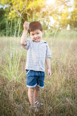 Happy little asian boy playing outdoors. Enjoy life. Cute asian boy on field. Imagens