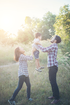 Happy young family spending time together outside in green nature park. Family love concept. Imagens - 77501076