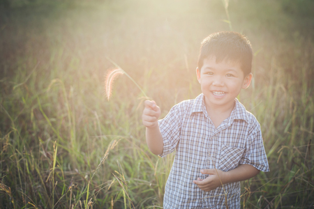 Happy little asian boy playing outdoors. Enjoy life. Cute asian boy on field. Imagens - 77501077