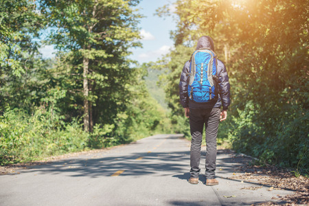 Rear of hiker man walking on the rural road on vacation. Holiday tourism concept. Imagens