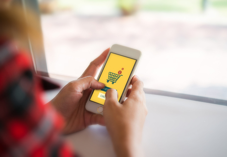Woman hands holding phone with online shopping on the screen. Freedom shopping online anywhere.