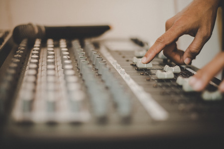 Man hands of sound engineer adjusting audio mixing console.