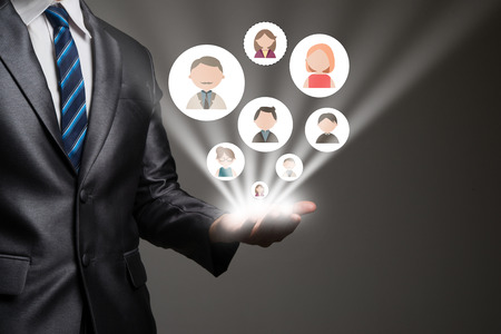 Young businessman pointing  digital peopl network connection icons on his hand. Imagens