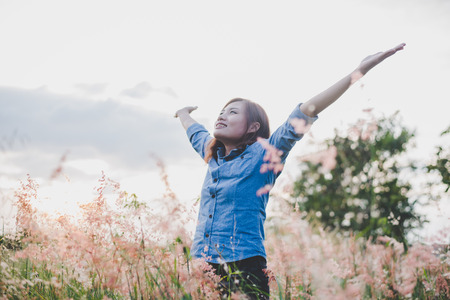 Young beautiful woman standing stretch her arms in the air on the grass field. Woman enjoy with nature during sunset. Imagens