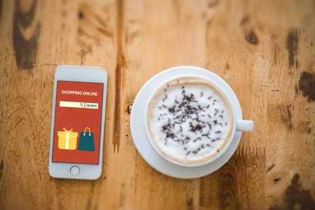Smartphone with online shopping on the screen near the cup of coffee on wooden table. Imagens - 77503141