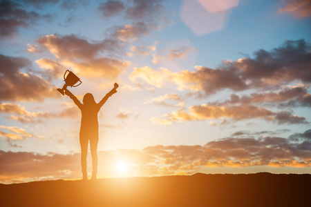 Happy celebrating winning success woman at sunset. Silhouette of young woman with bouquet in hand. Imagens
