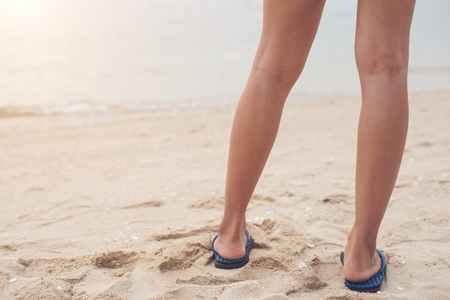 Young woman legs in flipflop sandals on sea beach.