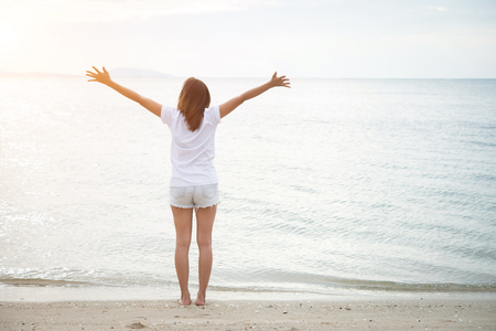 Rear of young woman standing stretch her arms in the air on the beach with barefoot. Relaxing holiday.