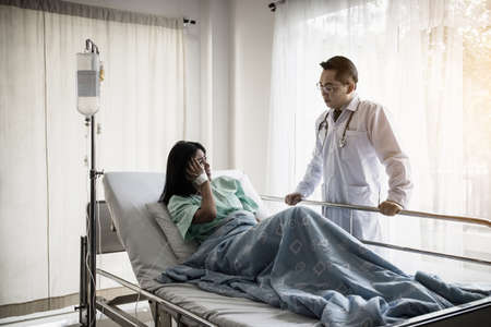 Medical doctor talking to patient and comforting her. Female patient having injury lying on bed at hospital. Standard-Bild