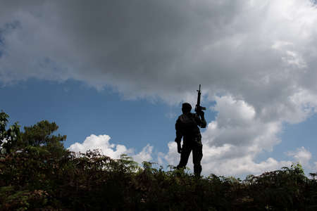 Military silhouettes of soldiers ready his weapon.
