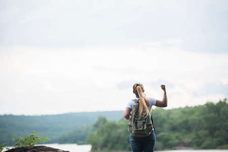 Close up back of tourist girl with arms raising happy with nature near lake. Travel concept.