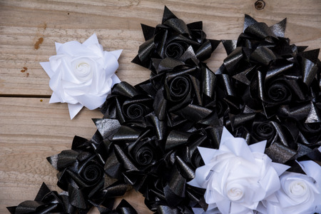 woebegone: black and white plastic flower on wood pallet background