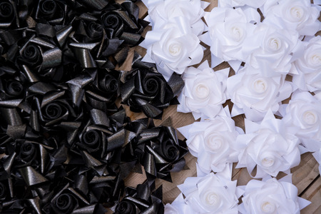 sorrowfully: black and white plastic flower on wood pallet background