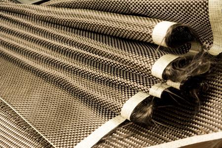 Black carbon fiber composite raw material close up background