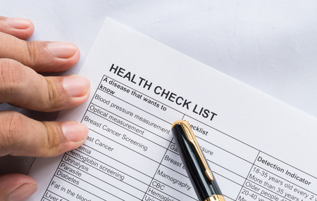 Person health check list paper with hand