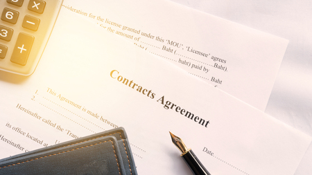 contract agreement document for sign with pen under orange worm shade
