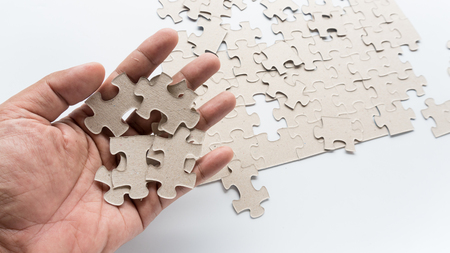 Hand put missing jigsaw puzzle into the paper board