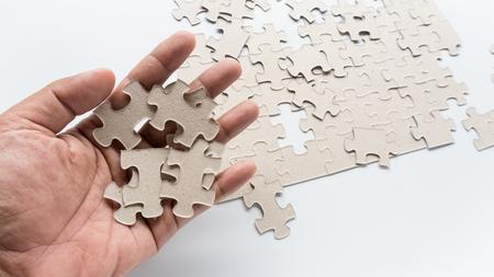 Hand legte fehlendes Puzzle in die Pappe