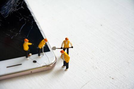 figurine model repair mobile crash with repairman Reklamní fotografie