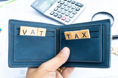tax and vat keyword on wood block in the money wallet with finance paper