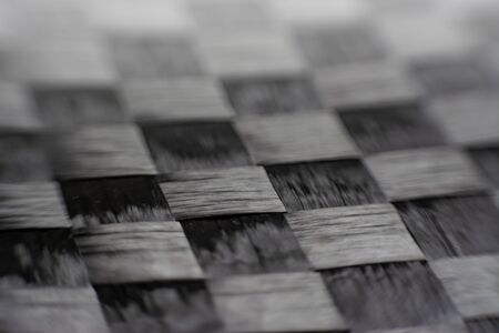 close up macro detail of carbon fiber composite material. strong light beauyful woven texture.