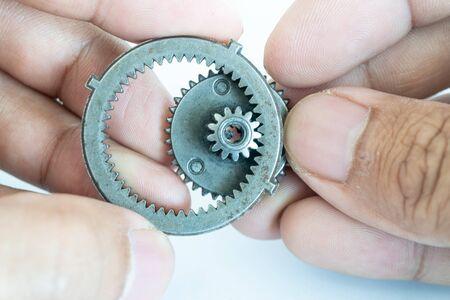 Small gear on hand concept of team driving Standard-Bild - 142932062