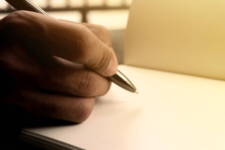 Hand holding a pen for sign business document notebook
