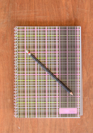 Notebook with black pencil on wooden table photo