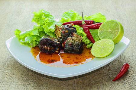 vegetable tin: Fish with Chili Sauce on the wooden floor. Stock Photo