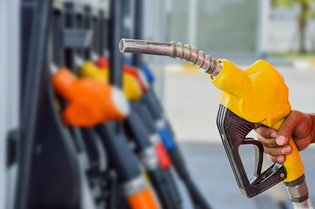 Holding a fuel nozzle against with gas station blurred background. Stock Photo