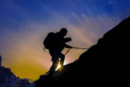 mountaineer: Silhouette of mountaineer and sunset. Stock Photo