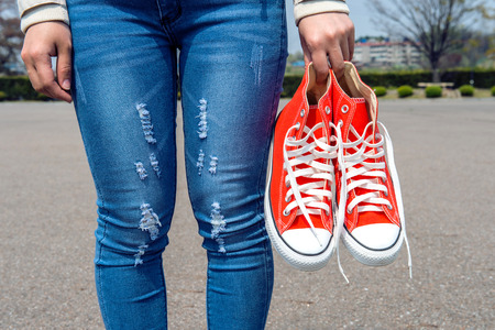 red jeans: woman hand holding a red sneakers. Stock Photo