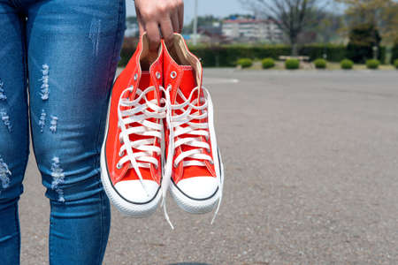 woman hand holding a red sneakers with space for text or symbol. photo