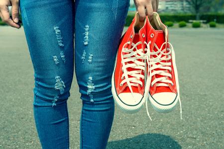 in jeans: mano de la mujer que sostiene una zapatillas de deporte de color rojo con el color de la vendimia.