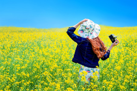 lighthearted: Young woman standing in yellow rapeseed field.