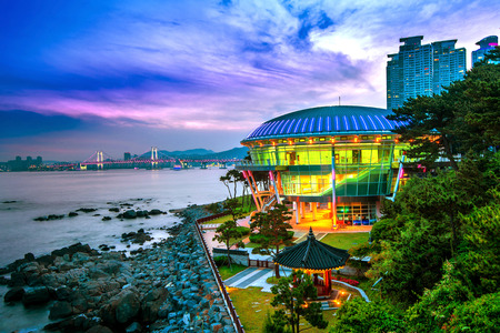 south korea: Dongbaek island with Nurimaru APEC House and Gwangan bridge at sunset in Busan,South Korea