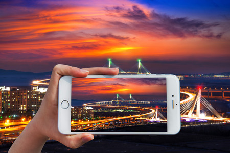 incheon: Hand holding smart phone take a photo at incheon bridge with sunset