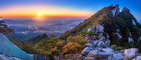 Salida del sol en Baegundae pico y las montañas Bukhansan en otoño, Seúl, en Corea del Sur.