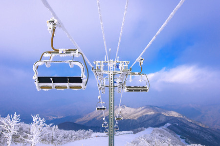 snowboard: Ski chair lift is covered by snow in winter, Korea. Stock Photo